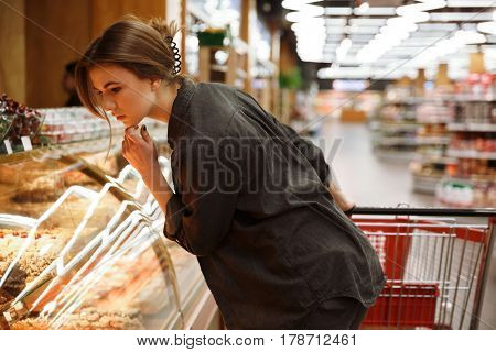 Image of concentrated young lady standing in supermarket choosing pastries. Looking aside.