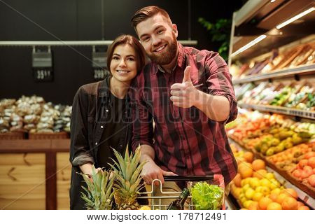 Image of young cheerful loving couple in supermarket with shopping trolley choosing fruits. Looking at camera showing thumbs up.