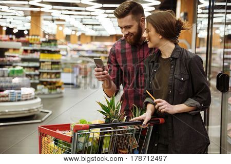 Image of young happy loving couple in supermarket with shopping trolley choosing products. Looking at mobile phone.