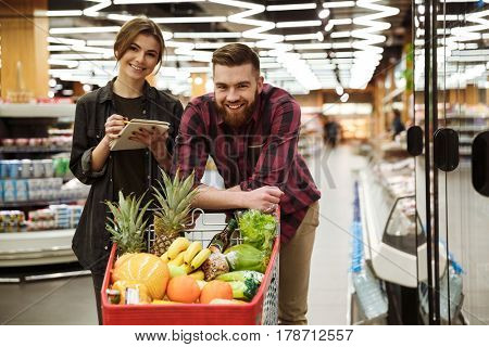 Image of young happy loving couple in supermarket with shopping trolley choosing products. Looking at camera.