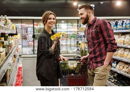 Photo of young cheerful loving couple in supermarket with shopping trolley choosing products. Woman looking at camera.