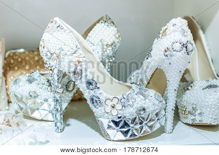 Bright wedding shoes are decorated with different precious stones and beads