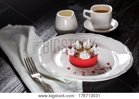 Caramel cheesecake with cream and flowers on the wooden background. A cup of coffee and a cake on a white plate