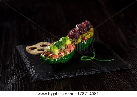 Salmon tartare and avocado salad on a black background. The original presentation of the dishes from the chef