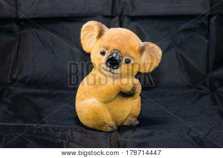 A brown fuzzy saving koala bear bank