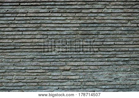 A wall made of layers of gray granite
