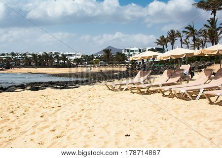 Sun loungers on sand in Playa Las Cucharas beach in Costa Teguise Lanzarote Canary islands selective focus
