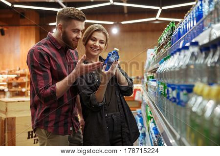 Photo of young happy loving couple in supermarket choosing water. Looking aside.