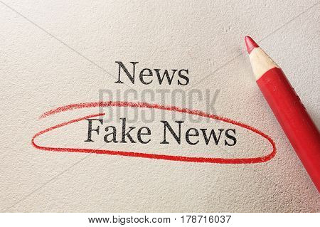 Red pencil with Fake News circled on textured paper