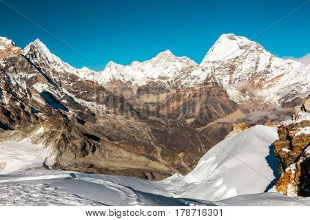 Daylight high Altitude Mountains View with heavy deep Snow and Rock Cliff on Foreground