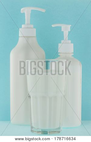 Glass of fresh milk next to white pump bottle of shower gel cream, body lotion on light blue background