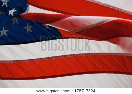 us flag back lit blowing in the wind