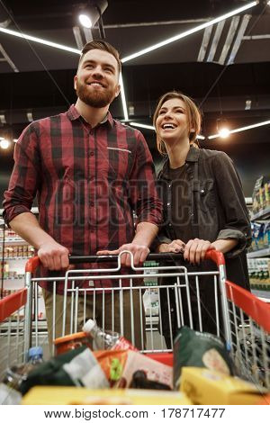 Image of happy young loving couple in supermarket with shopping trolley choosing products. Looking aside.
