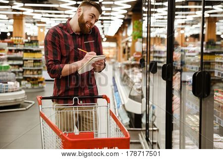 Image of cheerful young man standing in supermarket choosing products while talking by phone and writing notes at notebook. Looking aside.