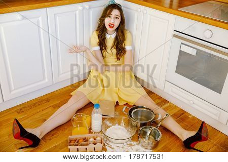 Photo of confused young pin-up woman with red lipstick sitting on floor at kitchen and cooking. Looking at camera.