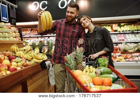 Photo of happy young loving couple in supermarket with shopping trolley choosing fruits. Looking aside.