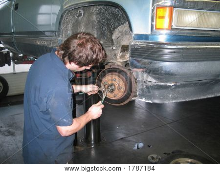 Car Mechanic Working On Brakes