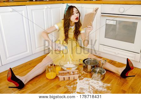 Photo of beautiful concentrated young pin-up woman with red lipstick sitting on floor at kitchen and cooking. Looking aside and reading recipe book.