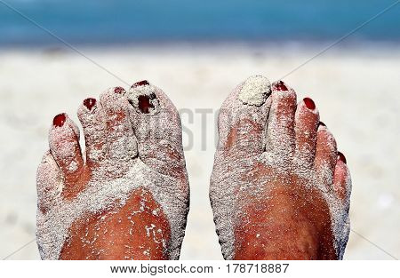 Sandy feet with painted toe nails on the beach