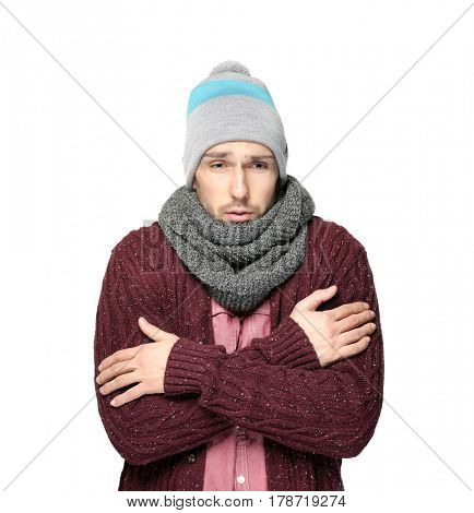 Young man in warm clothes shivering from cold on light background
