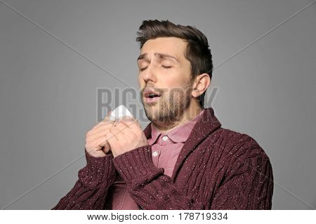 Young man sneezing in tissue on gray background