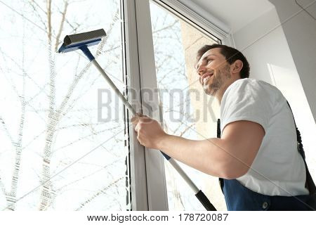 Young man washing window in office