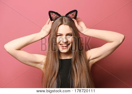 Beautiful young woman with cat ears on color background