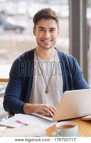 Modern working type. Portrait of young stylish guy using laptop while sitting at light office.