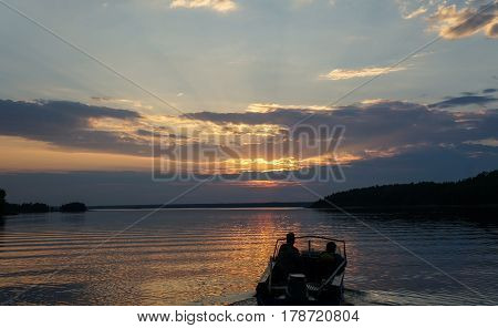 Picture of sundown on lake with floating boat and people