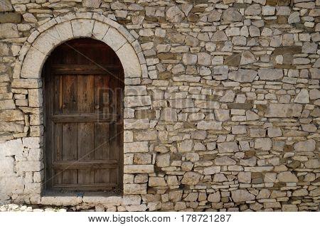 BERAT, ALBANIA - OCTOBER 01, 2016: Stone wall with old wooden door in Old town Berat, Albania on October 01, 2016.
