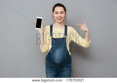 Portrait of a smiling happy pregnant woman pointing finger at blank screen mobile phone isolated on a gray background