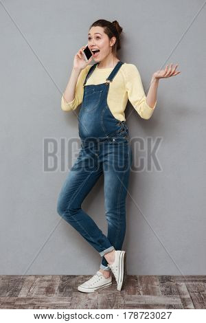 Full length portrait of a cheerful excited pregnant woman standing and talking on mobile phone isolated on a gray background