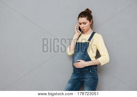 Worried depressed young pregnant woman talking on mobile phone isolated on a gray background