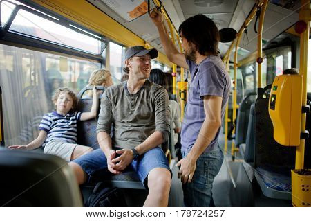 Passengers in the city bus. One man sits on a seat another stands nearby. They smile each other. At a window the boy sits. Modern public transport is convenient for children and adults.