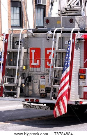 American flag hanging off the rear of a ladder fire truck.