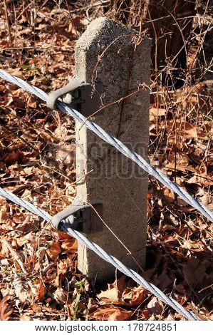 Old style wire guardrail with concrete footing.