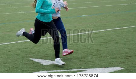 Two female high school athletes sprinting on a turf field during practice