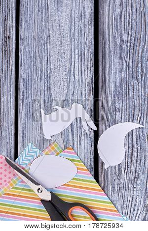 Animalistic figures cut from paper. Scissors on colorful paper sheets. Easter handmade decor.