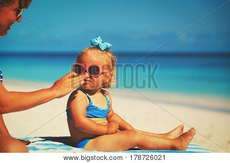 mother applying sunblock cream on daughter face, sun protection