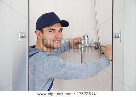 Young handsome plumber fixing faucet in shower stall