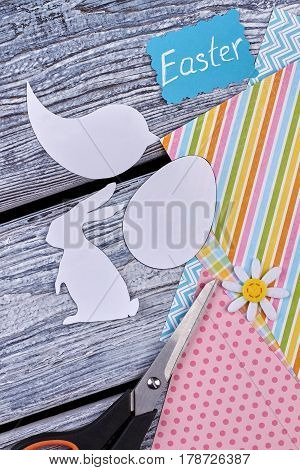 Papercut figures and colorful paper sheets. Easter card, scissors on wood. Handcrafting for a holiday.