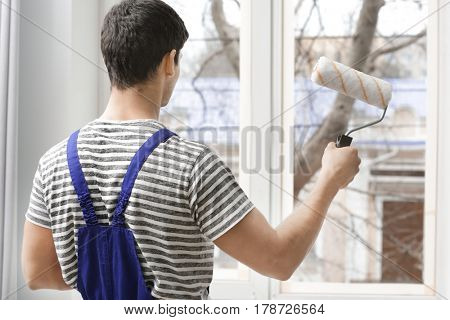 Young worker painting window in office