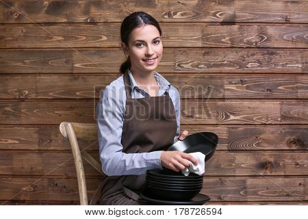 Woman wiping plate with napkin on wooden background