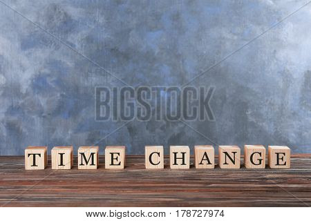 Cubes with text TIME CHANGE on table against color wall