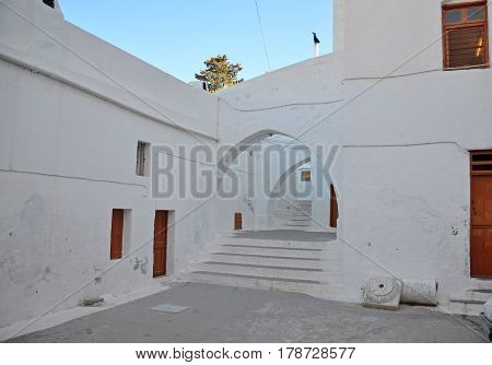 View of the courtyard between the oriental white buildings with wooden doors and arched gateway to the Mediterranean Sea with a concrete floor under a blue sky