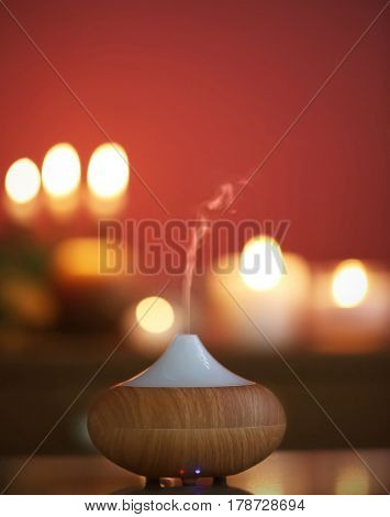 Aroma oil diffuser on blurred candlelight background