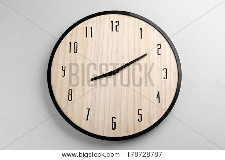 Big clock hanging on light wall