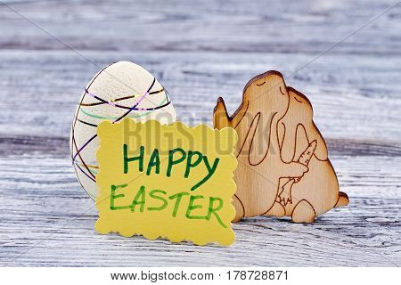 Easter decorations on wooden background. Styrofoam egg and plywood rabbits. Creative ideas for Easter decor.