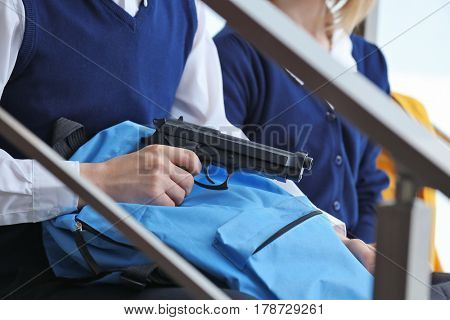 Closeup of schoolboy hiding gun in backpack