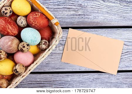 Blank card and Easter basket. Empty paper, gray wood background. Invite friends for Easter picnic.